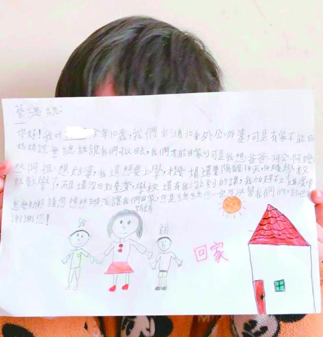 被困在武漢的台灣學童寫信給蔡英文總統,內容提到「我要回家、我要上學」,甚至有學童提到「我們在這裡連飲食都有問題,希望蔡總統能給我們一條回家的路」。圖為10歲男童舉著寫給蔡總統的信。(圖:湖北武漢台胞返鄉自救會提供)