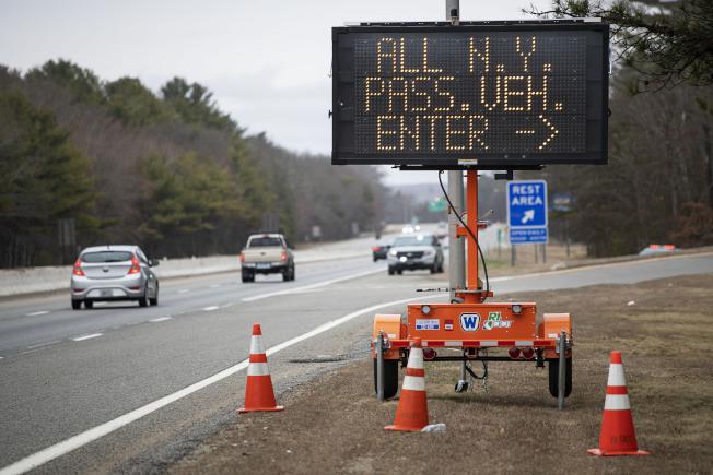 新冠疫情爆發期間,各州嚴防紐約州居民外出,限制病毒傳播,但被視為違憲。圖為3月底時羅德島州高速路旁告示牌要所有紐約州車牌的車輛停車檢查,遭到紐約州的違憲提告威脅。(美聯社)