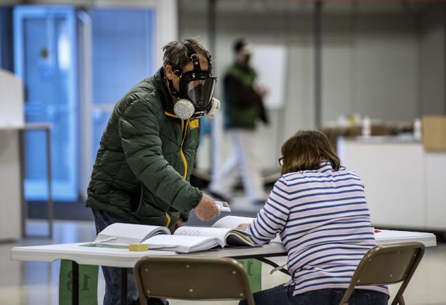 威斯康辛州7日舉行總統初選,圖為一名男子戴上全罩式雙罐面罩進入投票所。(美聯社)