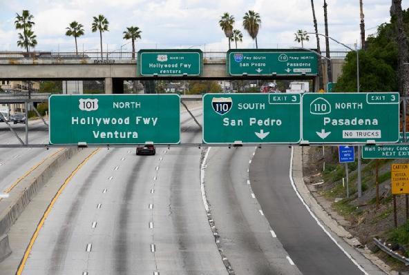 全美疫情持續嚴峻,多州厲行「居家避疫」措施,至少延續到月底。圖為加州洛杉磯鬧區7日公路上不見一輛車子。(美聯社)