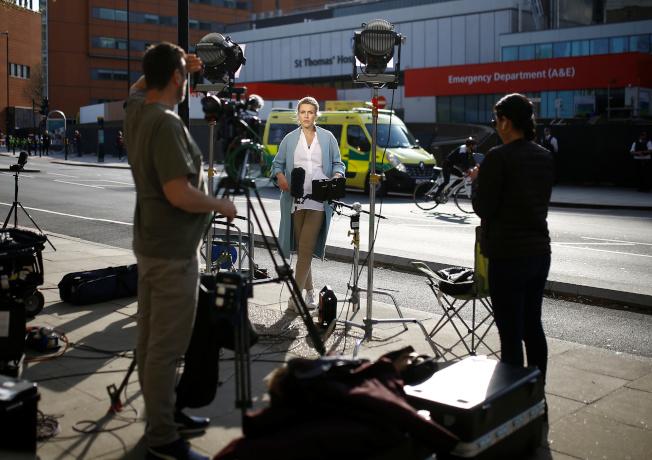 大批媒體7日在英國首相強生入住的醫院外守候。(路透)