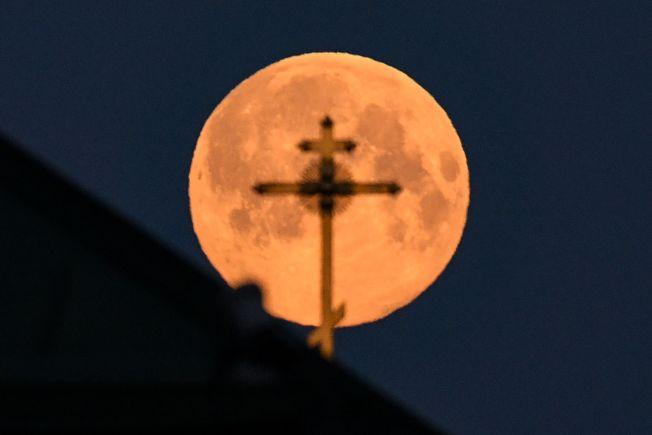 在俄羅斯市區,超級月亮與教堂上的十字架有了最佳的融合畫面。(Getty Images)