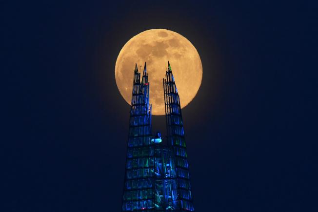 在倫敦,碎片塔( the Shard skyscraper)和超級月亮交織成魔幻畫面。路透