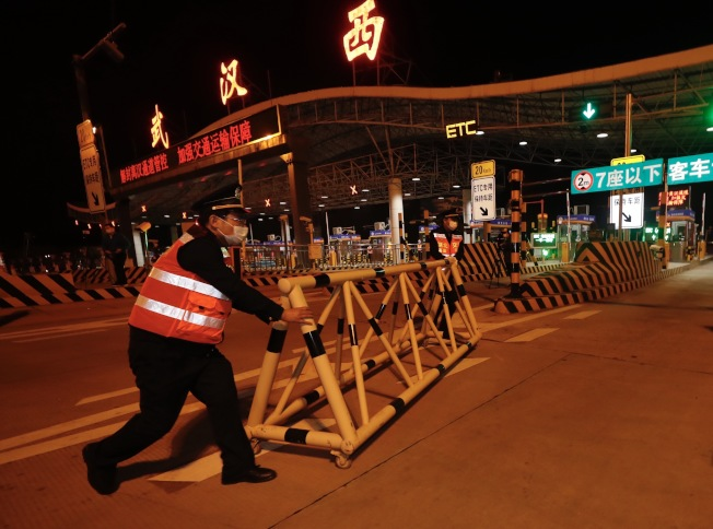 在武漢西高速收費站,工作人員8日凌晨移除圍欄。4月8日零時起,武漢市正式解除離漢離鄂通道管控措施,有序恢復對外交通。(新華社)