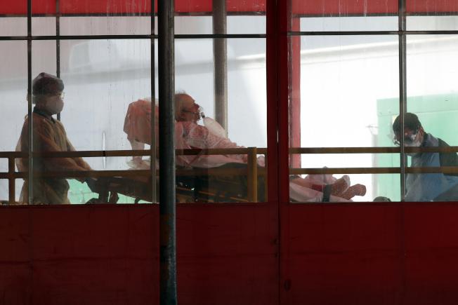 紐約皇后區艾姆赫斯特醫院(Elmhurst Hospital),醫護人員正轉移一名患者到救護車上。(美聯社)
