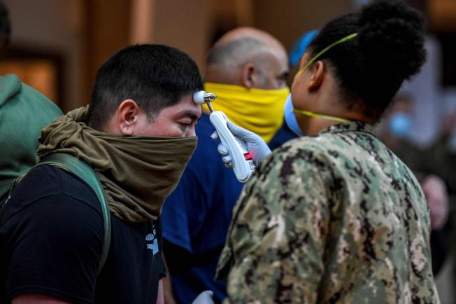 官兵被要求用乾淨的衣物當成口罩,遮蔽臉部。(Getty Images)