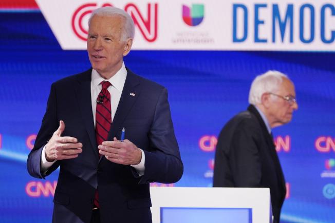 參選人桑德斯桑參議員(右)8日宣布停止競選活動,等於宣告前副總統白登成為準民主黨總統提名人。圖為今3月兩人辯論時神情。(美聯社)