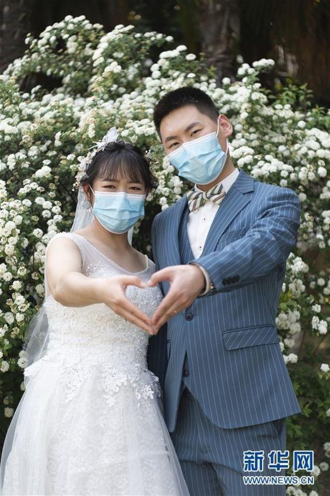 在襄陽市老龍堤公園,有人戴口罩拍攝婚紗照。(取材自新華網)
