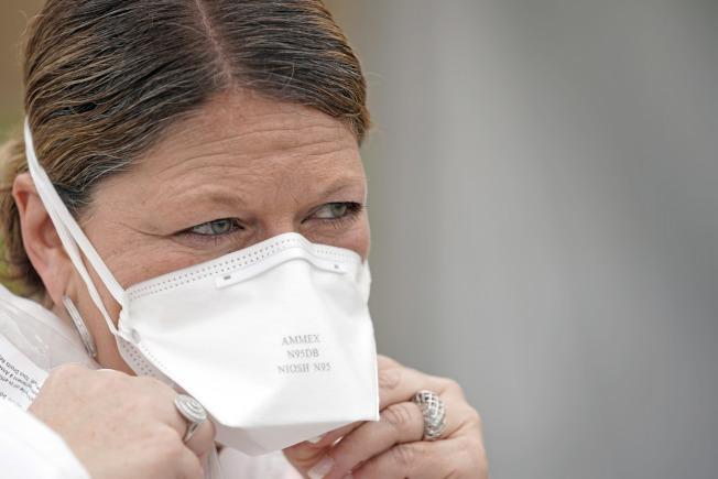 醫院主管和地方官員說,由於正常貨源供應不繼,有些人買到連基本品質測試都不合格的N95口罩,根本無法過濾傳染性強大的新冠病毒。圖為一名護士配戴N95口罩。(美聯社)