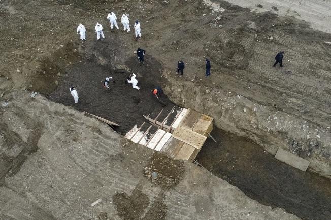 媒體9日利用空拍機,拍到穿著防護裝的工作人員將簡易棺木埋進紐約市哈特島公墓的壕溝內。隨著新冠肺炎死者數大增,紐約市已修改政策,加速死者下葬。美聯社