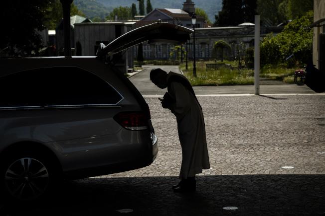義大利杜林(Turin),一位牧師面對放置新冠逝者遺體的棺材祈禱。(美聯社)