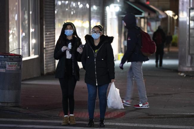 疫情下的紐約布朗士街道安靜,兩旁店鋪幾乎都關了門,路上行人戴著口罩。(美聯社)
