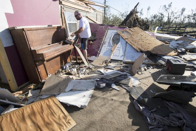 奧克拉荷馬州、德州和路易斯安納州遭受多個疑似龍捲風的風暴襲擊,造成至少七人死亡。圖為德州歐納拉斯卡的居民,在被毀住家中找錢包。(美聯社)