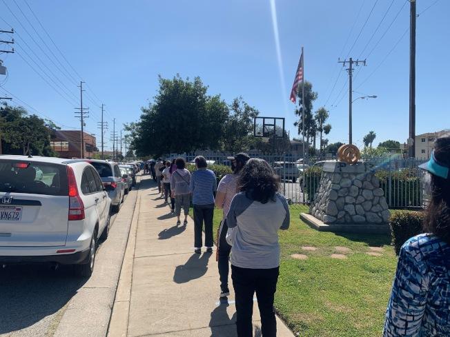 基督教角聲醫療中心和85度C24日聯手在聖蓋博發放口罩和麵包給民眾。(記者張宏/攝影)