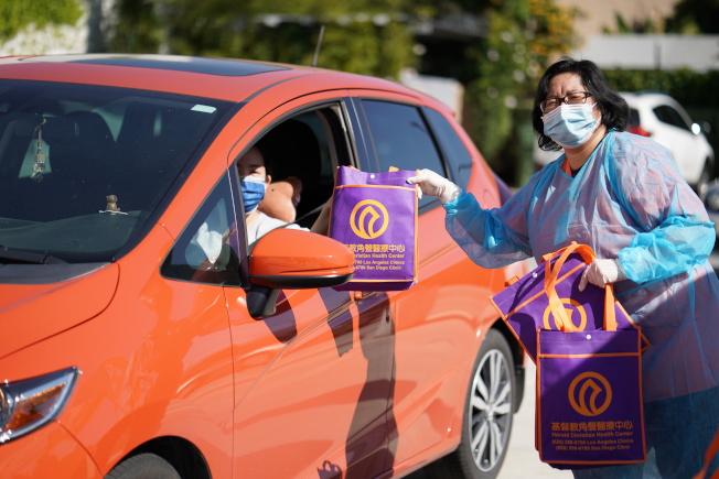 基督教角聲醫療中心和85度C24日在羅斯密市發放口罩和麵包。(讀者提供)