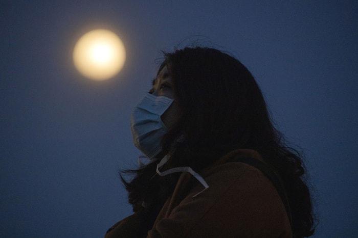 在中國武漢,一位戴口罩的女子與超級月亮的合影。美聯社