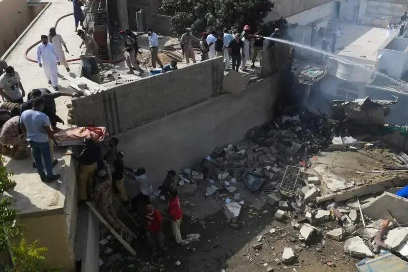 巴基斯坦國航一架客機驚傳墜毀住宅區,圖為搜救人員搬運遺體。 Getty Images