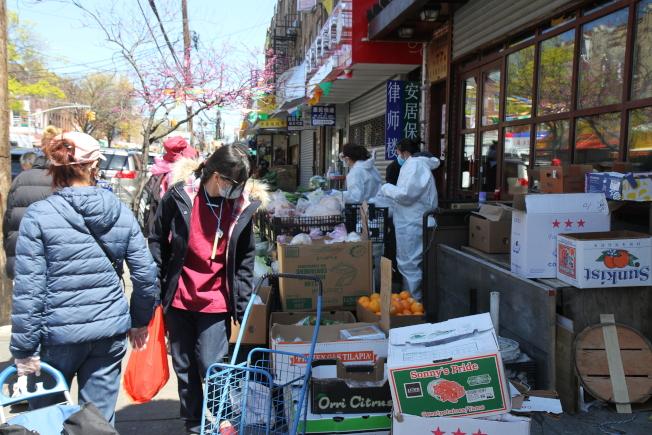 華人穿著防護服街邊賣菜。(記者黃伊奕/攝影)