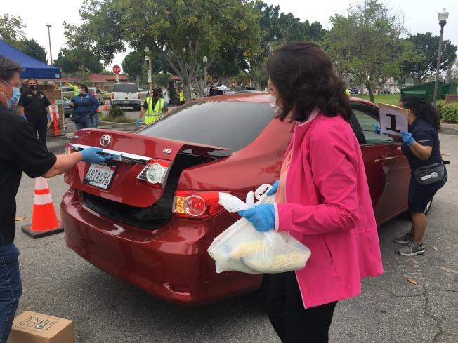 縣政委員蘇麗絲向民眾分發食物。(記者王全秀子/攝影)