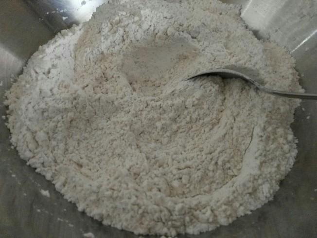 1.倒入麵粉、酵母、黑芝麻粉、紅糖、核桃和鹽,充分攪拌均勻。