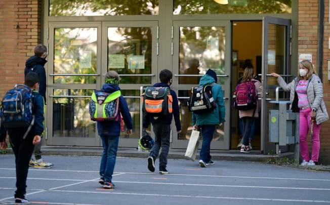 德國部分學校已經重開。7日,德國西部一所小學迎接學生返回校園。圖中,學生保持社交距離,一一走進學校。(Getty Images)