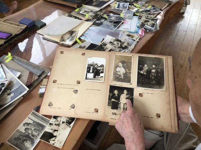 日裔George Uno在日本的家中翻閱老照片。(PBS提供)
