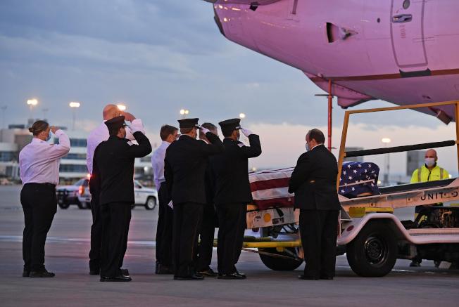 從科羅拉多州到紐約支援抗疫的醫療志工凱瑞感染新冠肺炎離世,遺體運回家鄉,同僚和家人在丹佛市機場迎接靈柩。(美聯社)