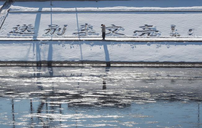 新華社推出1萬6000字長文,其中提到李文亮醫師非「吹哨人」,圖為北京民眾在積雪上留下「送別李文亮」的文字。(中新社)