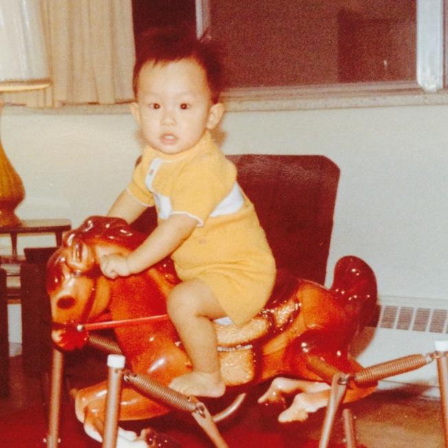 作者孩子一歲多時騎在木馬上的照片。