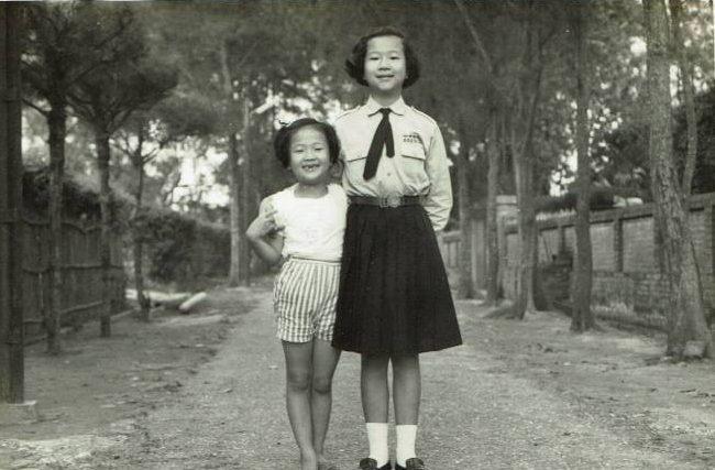 大姊與我在台南的糖廠宿舍合影。圖左邊是我家的竹籬笆,右邊是於梨華父母家的「豪華」磚牆。照片提供/張瑩瑩