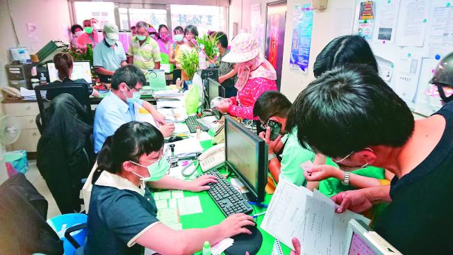 農漁民紓困補助申請11日上路,彰化區漁會王功辦事處擠滿人潮,許多人在辦公室外填寫表格,希望能盡快領到紓困金。(記者簡慧珍/攝影)