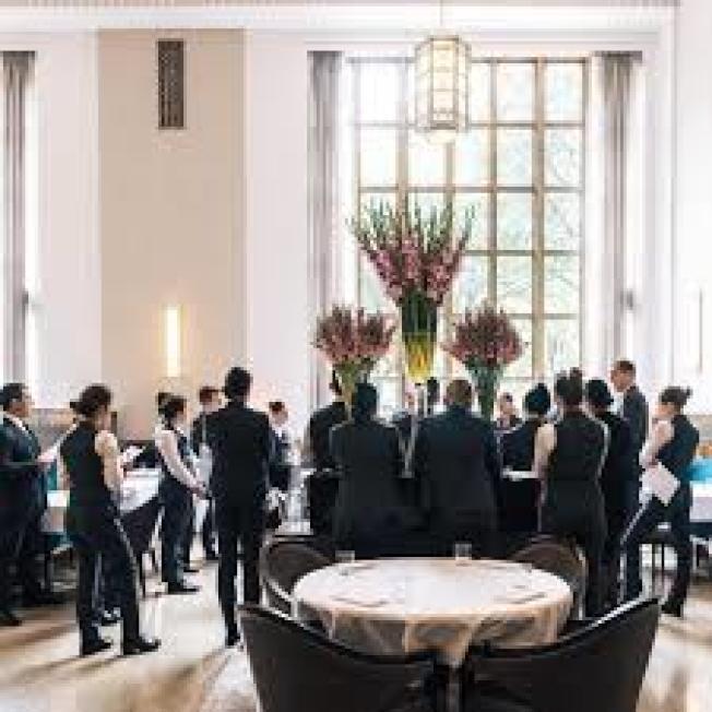 全球最佳餐館之一的紐約曼哈頓「麥迪遜公園11號」因疫情關門,可能不會重開。圖為該餐廳服務生營業前聚集開會的景像恐不再。(取自臉書)