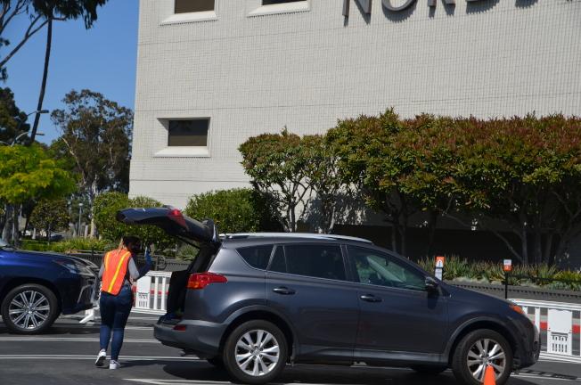 顧客抵達取貨地點打開汽車後備箱,就有專人將貨品送達並放在後備箱內。(記者王全秀子/攝影)