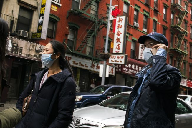 被新冠疫情掃過,全美餐館陷入重新開業復工的挑戰,尤其以中餐館業壓力最大,原有顧客不敢到華埠消費。圖為路人戴著口罩走過紐約華埠。(路透)
