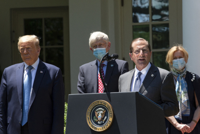 報導指抗疫後半工作,川普總統(左)有意讓各州負責。同時衛福部長阿查爾(右二)17日受訪時表示,解封地區未見新冠病例增加。 (美聯社)