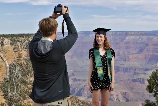 大峽谷國家公園日前開始逐步重新開放,圖為一名大學應屆畢業生在峽谷旁拍照留念。(美聯社)