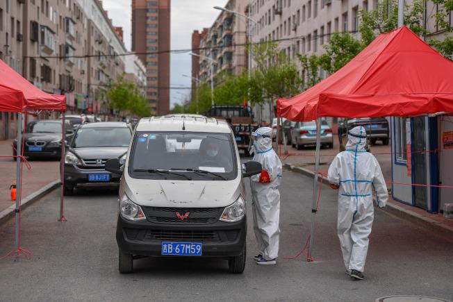 5月18日,在舒蘭市通機小區,工作人員為出入居民測溫登記。(新華社)