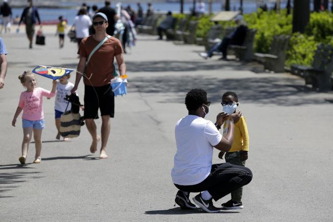 CDC證實兒童神秘炎症與新冠有關,圖為在布朗士的果園海灘前,一名男子調整了孩子的口罩。(美聯社)