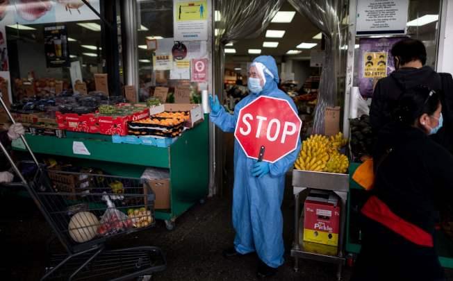 紐約市皇后區一家超市前,員工穿著防護服,手舉「停」標識。(Getty Images)