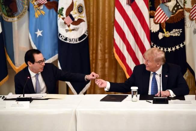 川普總統19日在白宮內閣會議上,從財政部長米努勤手上接過一張現金卡,國稅局將會寄出紓困金現金卡給符合資格的民眾。(美聯社)