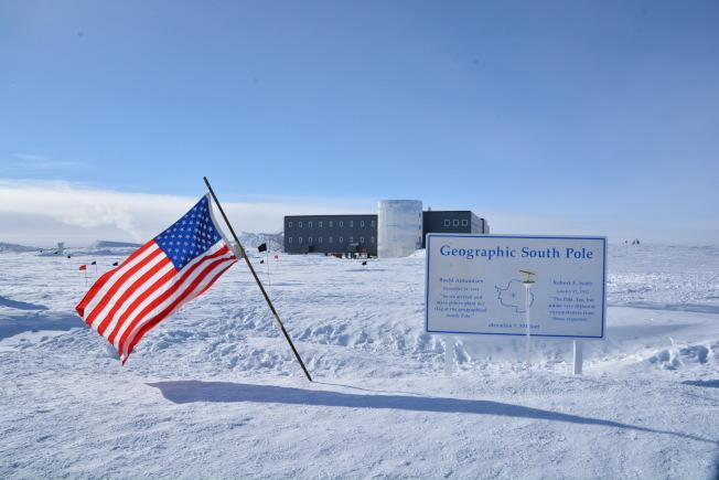我們此刻正牢牢地站在南緯90度的南極點上,身邊飄揚著美國國旗下的探險立牌上刻著:南緯90度, 地理南極點,羅爾德·阿蒙森1911年12月14日(抵達南極點),斯科特1912年1月16日(抵達南極點)。