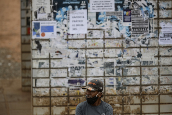 在歐美富裕國家紛紛復工之際,新冠疫情在窮國卻開始擴散。圖為巴西一名戴著口罩的市民在公車站裡。(美聯社)