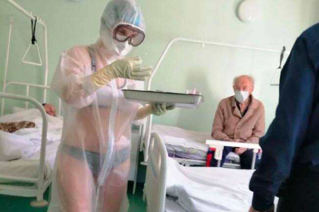 俄國女護士防護衣下僅穿內衣,一名戴口罩男病患緊盯著她。(取自Instagram)