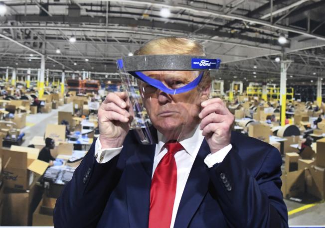 川普總統21日參觀密西根福特汽車廠時,雙手舉著一個有福特商標的面罩,但並未戴上。(美聯社)