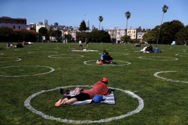 舊金山市中心米慎區的多洛斯公園(Dolores)平時人擠人,大家都喜歡到這裡享受陽光。為了避疫,人們發明了圖中的「社交圈」,讓圈與圈之間保持社交距離。(美聯社)
