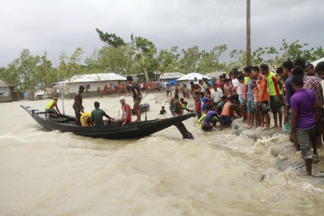 孟加拉低窪地區大淹水,民眾紛紛搭船逃離。 (美聯社)