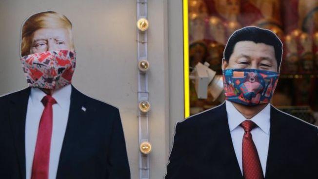 新冠肺炎蔓延全球,中國與美國政府就新冠病毒疫情的口水戰不止,川普及習近平的立牌被戴上口罩。(路透)