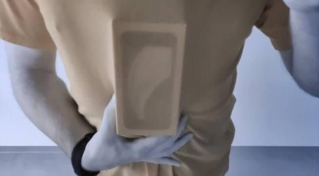 實際測試發現,Oneplus 8 Pro手機拍攝時衣物變成肉色,且能看出盒子上的印刷以及男子的胸部特徵。(視頻截圖)