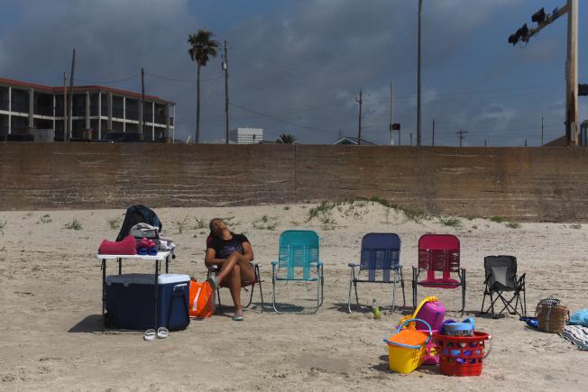 民眾準備在國殤日周末外出,公衛專家擔憂群聚恐導致疫情回升。圖為德州海灘上的遊客。(路透)