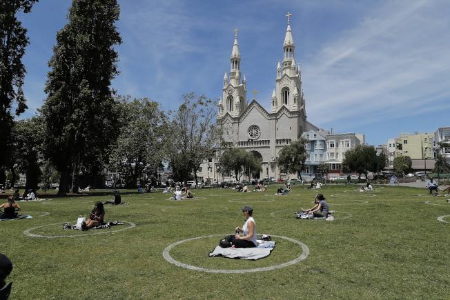 國殤日長周末來了,民眾群聚恐導致疫情回升。圖為舊金山聖彼得和保羅教堂前,民眾坐在畫著白圓圈的草地上,保持社交距離 。(路透)